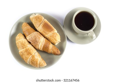 Cup of tea with fresh croissants on green plate isolated on white