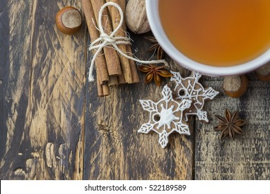 Cup of tea, ginger cookies and cinnamon on brown wooden table