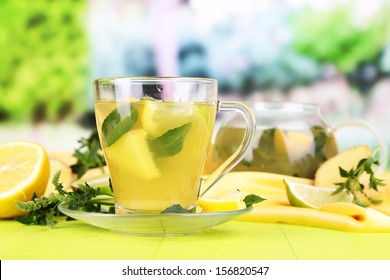 Cup of tea with ginger on wooden table on nature background