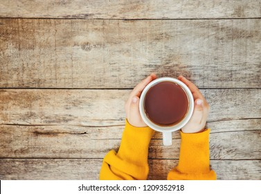 cup of tea in the hands of a child and a cozy autumn background. Selective focus. Kids.