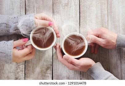A cup of tea in the hands of a man and a woman. Selective focus. cute.