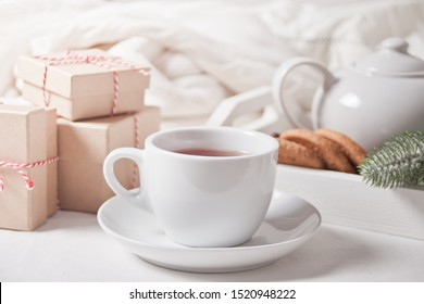 Cup of tea, homemade cookies, Christmas gift boxes and Christmas decor on the white background.