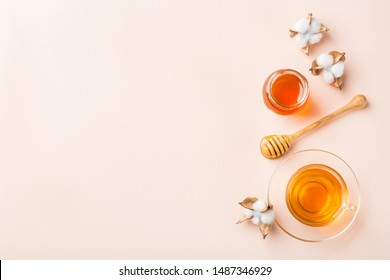 Cup of tea with honey on a trendy pastel pink, coral background. Copy space, flat lay