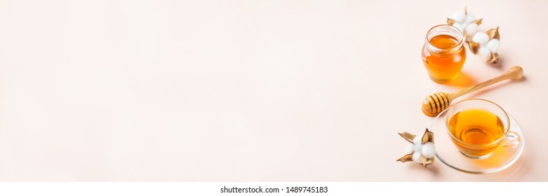 Cup of tea with honey on a trendy pastel pink, coral background. Copy space