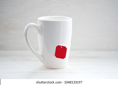 Cup of tea isolated on white wooden  background. Teabag with red label.