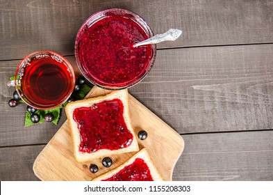 Cup of tea, jam in a bowl and bread with jam on a wooden cutting board, on a wooden boards background.