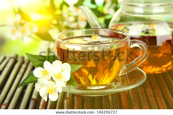 Cup of tea with jasmine, on bamboo mat, close-up