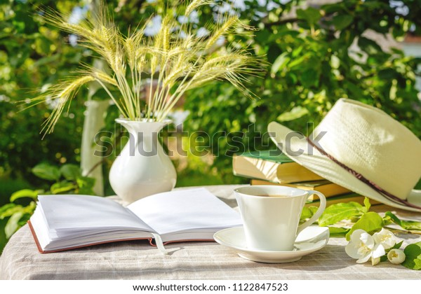 cup with tea, a laptop, a computer, a bookshine table in the garden on a summer morning, a place to work, a concept of freelancing