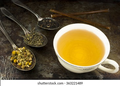 Cup of tea with leaves and honey / A cup of brewed green tea with honey sticks and loose leaf tea leaves