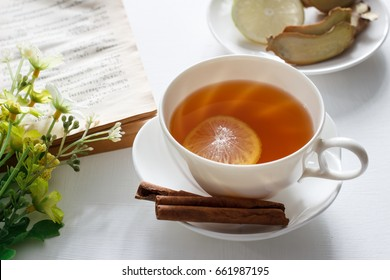 cup of tea with lemon, cinnamon and ginger on white table.