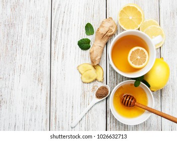 Cup of tea with lemon and ginger on a old wooden table