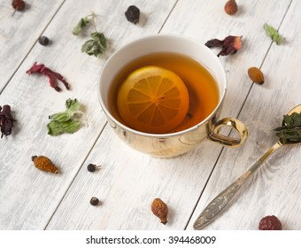 Cup of tea with lemon and spoon on a wooden table