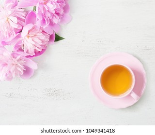 Cup of tea  and  light  pink peonies on   old white wooden table.
