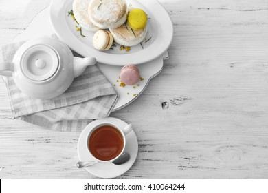Cup of tea with macaroons on wooden background
