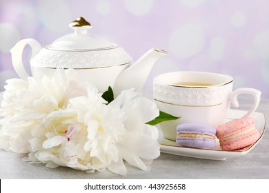 Cup of tea with macaroons and peonies on wooden table