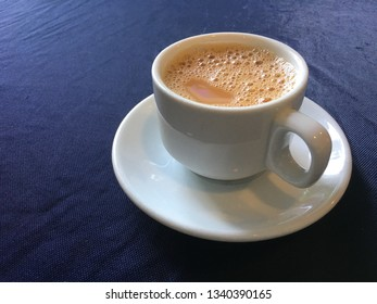 Cup of tea with milk on blue cloth.