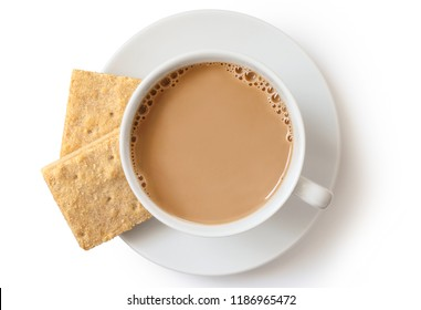 A cup of tea with milk and two square shortbread biscuits isolated on white from above. White ceramic cup and saucer.