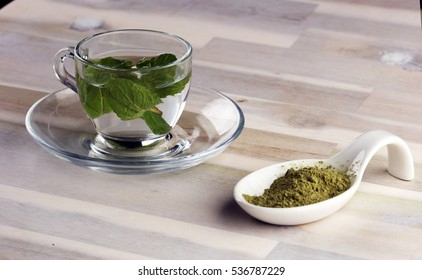 Cup of tea and mint leaf on a wooden background - hot water in a tearoom place