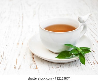 Cup of tea with mint on a old white wooden background