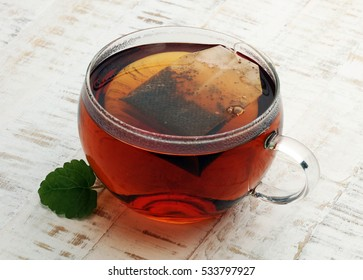 Cup of tea and mint on a wooden background - hot water in a tearoom place