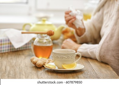 Cup of tea and natural medicine for cough on kitchen table
