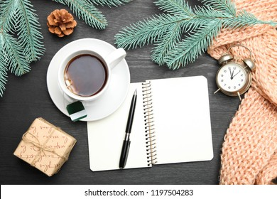 Cup of tea and notebook with pen on black background. Concept goals for new year.