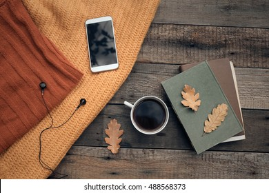Cup of tea with old book, autumn leaves on wooden table.
