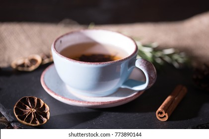 a cup of tea on a dark background, dried flowers and smoke