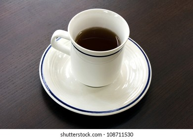 A cup of tea on dark brown wood surface