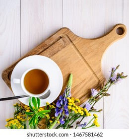 cup of tea on a saucer with a set of herbal tea thyme, mint, lemon grass on wooden rustic background top view close up copy space