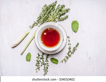 cup of tea on a saucer with a set of herbal tea thyme, mint, lemon grass on wooden rustic background top view close up