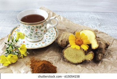 A cup of tea on a table with ginger and ground turmeric. Concept of health.