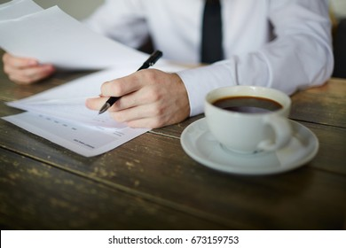 Cup of tea on table and hands of businessman signing papers