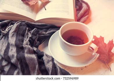 A cup of tea on a table with a striped warm scarf or stole and a book. Warm autumn. Toning and blur