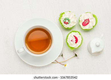 cup of tea on white table with christmas cupcakes