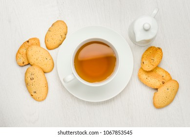 cup of tea on white table with cookies and milk jug