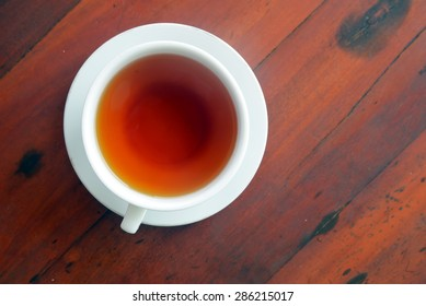 Cup of tea on a wood table, top view