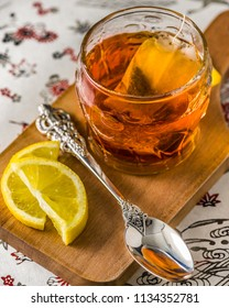 A cup of tea on a wooden serving board, silver tea spoon and slices of lemon