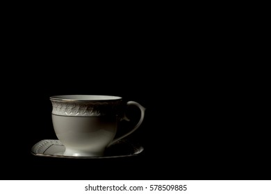 Cup of tea on wooden table with black background