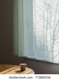 Cup of tea on a wooden table by the window with shades of tree branches