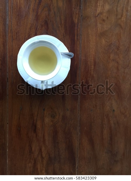 A cup of tea on wooden table with quit dark tone