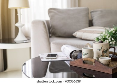 cup of tea on wooden tray on a round table with sofa in living room at home