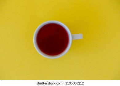 Cup of tea on a yellow background top view.