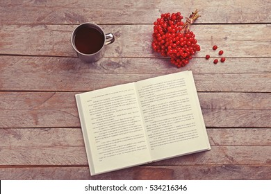 Cup of tea with open book and bunch of red rowan on wooden background