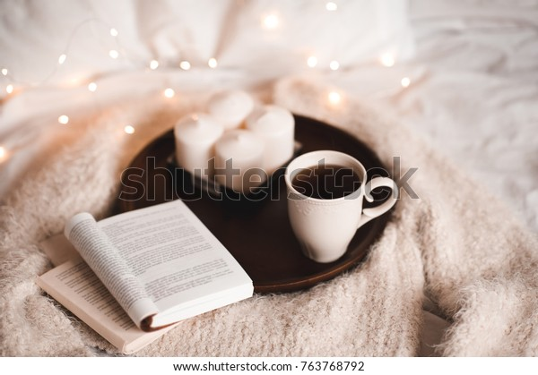 Cup of tea with open book on wooden tray with candles in bed. Good morning.