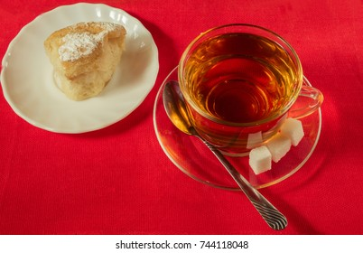 Cup with tea and pastry on a plate