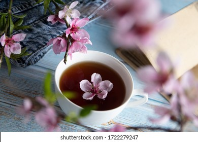 A cup of tea with a peach flower in it, surrounded by branches of peach flowers, jeans and notebook laying on a blue wooden background