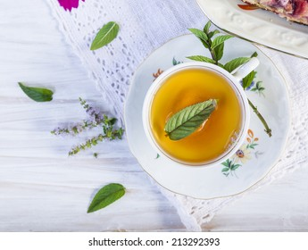 Cup of tea with peppermint on white wooden table with lacy napkin.