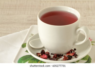 A cup of tea with petals, dry berries and fruits