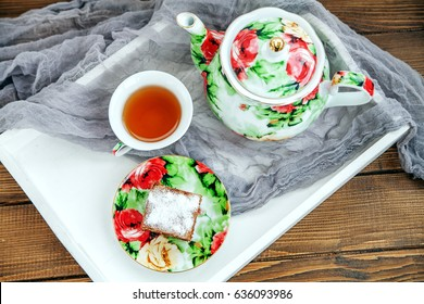 Cup of tea and piece of cake on a wooden tray. Top view. The concept of beverages and food.